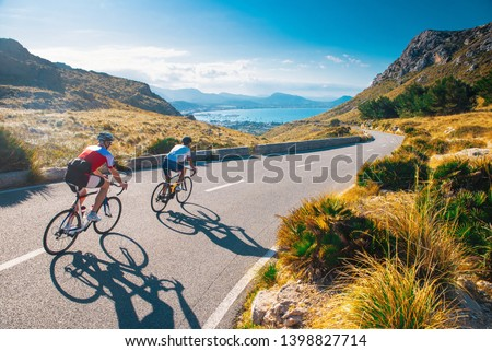 Road cycling photo. Two triathlete train in beautiful nature. Sea and mountains in background. Alcudia, Mallorca, Spain #1398827714