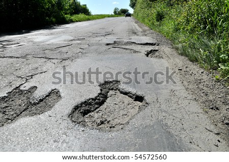 Road destroyed after winter. A hole in the road.