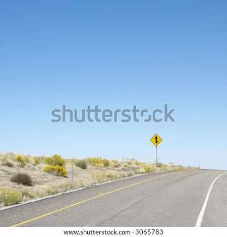Road disappearing into horizon with merge road sign.