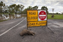 Road flooded sign on road in front of the flooded Condamine River in South East Queensland.