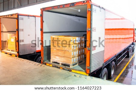Road freight industry logistics and transportation. Warehouse dock cargo load shipment into shipping container truck. Stack shipment boxes on pallet inside a truck.
