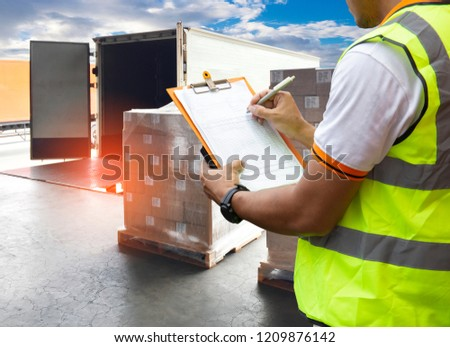 Road freight logistics and transportation. Warehouse worker courier holding clipboard checking cargo shipment pallets for load into a truck.