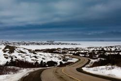 Road from Tilting to Joe Batt's Arm, two outport fishing villages at frozen North Atlantic Ocean winter landscape of Fogo Island, Newfoundland, NL, Canada