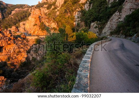 Road going through red cliffs in Corsica