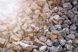 Road gravel and granite gravel texture. Crushed Gravel background. Pile of Stones texture with sunbeam lights. Industrial coals.