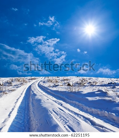 road in a winter snowbound plain by a sunny day