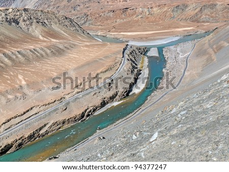 road in barren mountains along confluent rivers