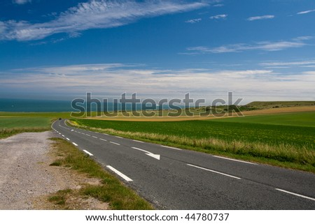 Road in countryside. Sea on the horizon