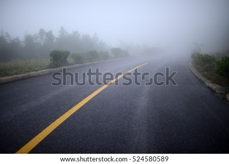 Road in heavy fog. A crooked road turn into mist. Full of mysterious, misty and dangerous feelings. #524580589