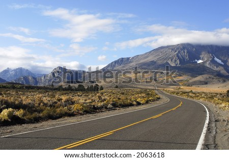 road in high desert leading to fall mountain scenery