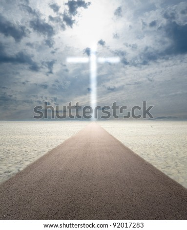 Road in sand leading to glowing cross