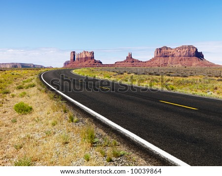 Road in scenic desert landscape with mesa and mountains.