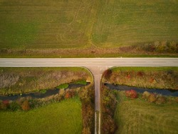 Road in the country with T-junction and bridge from above
