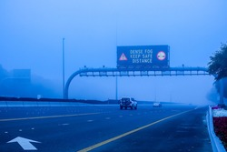 Road in the fog, sign mention keep distance for motorists at dubai road, foggy weather in UAE, Dense Fog keep Safe Distance banner in arabic and english