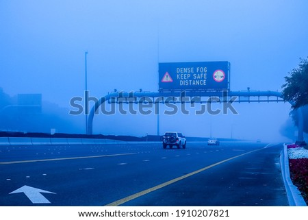 Road in the fog, sign mention keep distance for motorists at dubai road, foggy weather in UAE, Dense Fog keep Safe Distance banner in arabic and english Сток-фото ©
