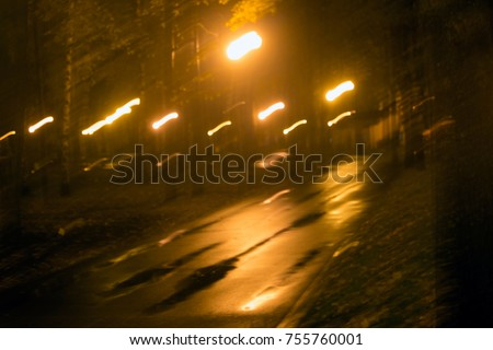 Road in the night park after the rain. Blurred photo