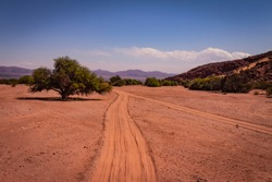 Road in the valley between mountains, arid mountain area. Reddish dirt road.