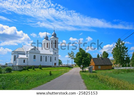 Road in the village with church and wooden house