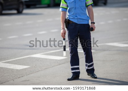 Road inspector with a baton.