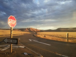 Road intersection-July 7,2014: Road intersection with stop sign in CA, USA. It's represent the concept of strategic dilemma choosing the right direction to go when facing two equal or similar options.