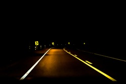 road into the dark with curve sign at night