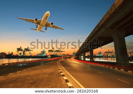 road ,land bridge run into ship port and commercial cargo plane flying above use for land ,air and vessel transport industry business