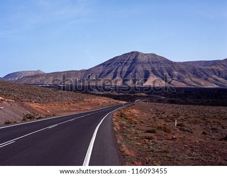 Road leading into one of the lava beds, Timanfaya National Park, Lanzarote, Canary Islands, Spain. - stock photo