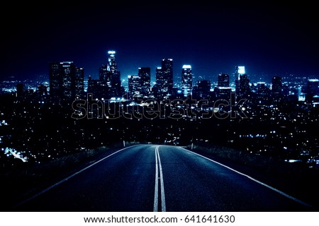 Road leading to modern illuminated night city. Forward concept
