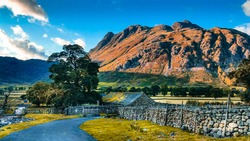 Road leading to picturesque stone cottage house next to a river with Great Langdale mountains and valley in the background at sunset time in the Lake District National Park in North West England, UK.