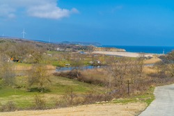 Road leading to the beach in the Black Sea town of Kiyikoy in northwestern Turkey with windfarms in the background