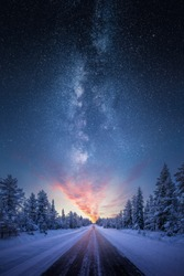 Road leading towards colorful sunrise between snow covered trees with epic milky way on the sky