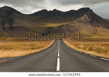 Road leads to a magnificent volcano mountain in the distance, in a dramatic scene in the Snaefellsjokull national park, Iceland.
