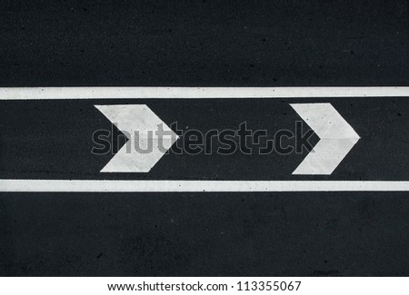 road marking: white arrows and line on the dark asphalt road.