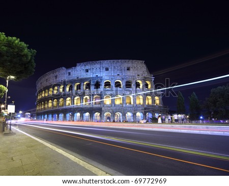 road near old stone walls of Coliseum at summer night in Rome, Italy