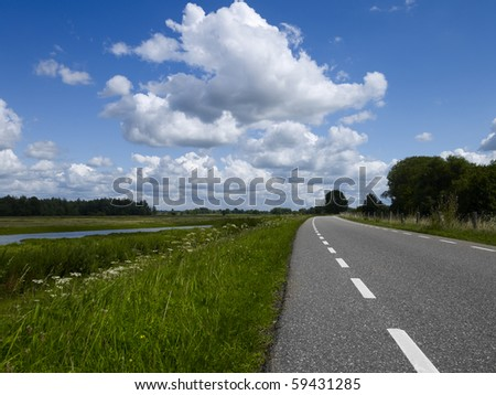 Road on a dike in a Dutch landscape with the river the Merwede near the old town of Woudrichem, province Noord-Brabant