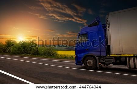 road on sunset. blue truck on the asphalt rural road #444764044
