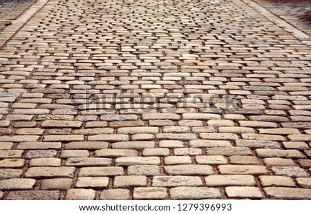 Road paved with paving stones. Cobbles background