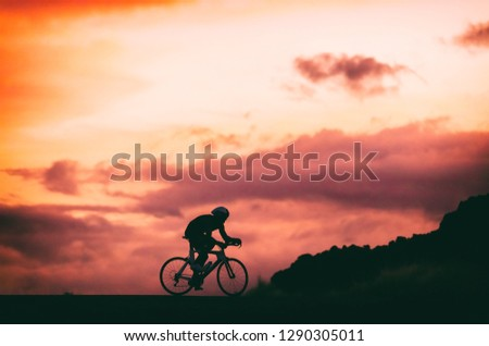 Road racing triathlete bike cyclist riding at night doing triathlon. Silhouette of male athlete training at sunset background.