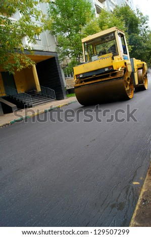 Road repair, compactor lays asphalt.