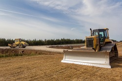 Road Roller and Bulldozer on the construction of a new road. Construction machinery. Dedicated Construction machinery for handling bulk materials