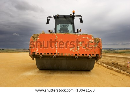 Road roller at worksite and cloudy sky