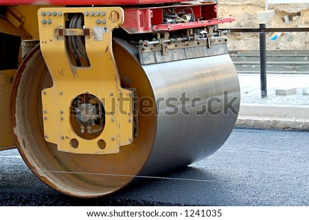 Road roller leveling fresh asphalt pavement