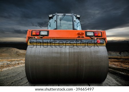 Road roller on the old highway until a big storm approaching.