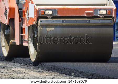 Road-roller pressing new asphalt