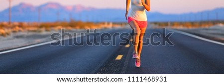 Road runner female athlete running shoes training on desert road banner. Panorama crop of lower body jogging outdoors at sunset. #1111468931