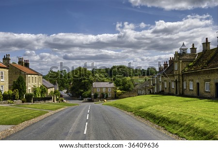 Road running through Coxwold village with cloudscape in background, Hambleton, North Yorkshire, England