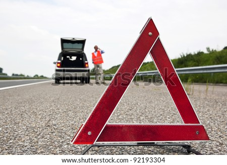 Road side warning triangle, warning oncoming traffic of a broken down car, with a man using his cell phone to call for assistance