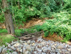 Road side washout erosion lined with rocks and broken tree brunches going down to a stream