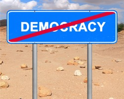 Road sign. Democracy termination location mark. The word democracy crossed out with a red line. It is written on a blue signboard and located opposite the stony desert landscape