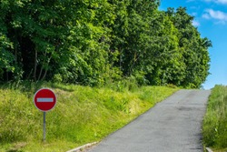 Road sign do not enter. There is no entry to that side. The road goes in the wrong direction. Green trees and blue sky